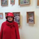 Лилия Юрьевна Корнилова на фоне выставки своих работ в ЦРБ им. Ф.М. Достоевского